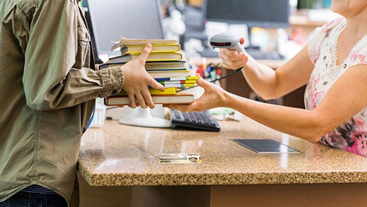 A librarian scanning a personalized library card with Badgy